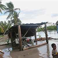 "A young boy on the South Pacific island of Kiribati, watches the sea during a ""king tide"" encroach on his families low lying land in Buota village."