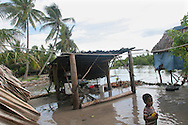 """A young boy on the South Pacific island of Kiribati, watches the sea during a """"king tide"""" encroach on his families low lying land in Buota village."""