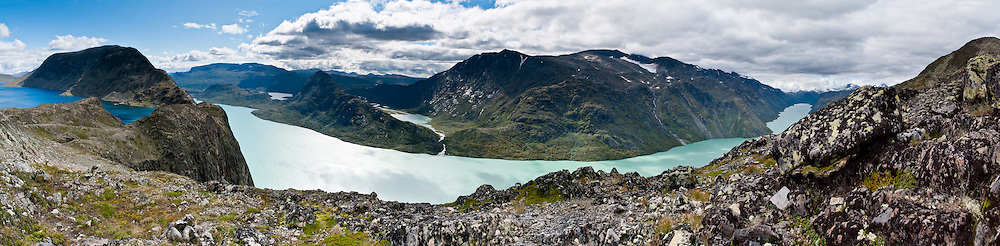 Besseggen is one of the most popular hikes in Norway. The mountain ridge of Besseggen (or Besseggi) rises between green Lake Gjende and blue lake Bessvatnet in Oppland county, in Jotunheimen (the Home of the Giants, the highest section of the Scandinavian Mountains), Norway. Ride a boat from Gjendesheim to Memurubu, then hike along the trail to narrow Besseggen at the halfway point. Then ascend to the trail's highest point, Veslfjellet (1743 meters), and walk steeply down to Gjendesheim, in about 8 to 10 hours total. Pretty Lake Gjende is colored green from glacier runoff containing clay (rock flour). Panorama stitched from 6 overlapping photos.