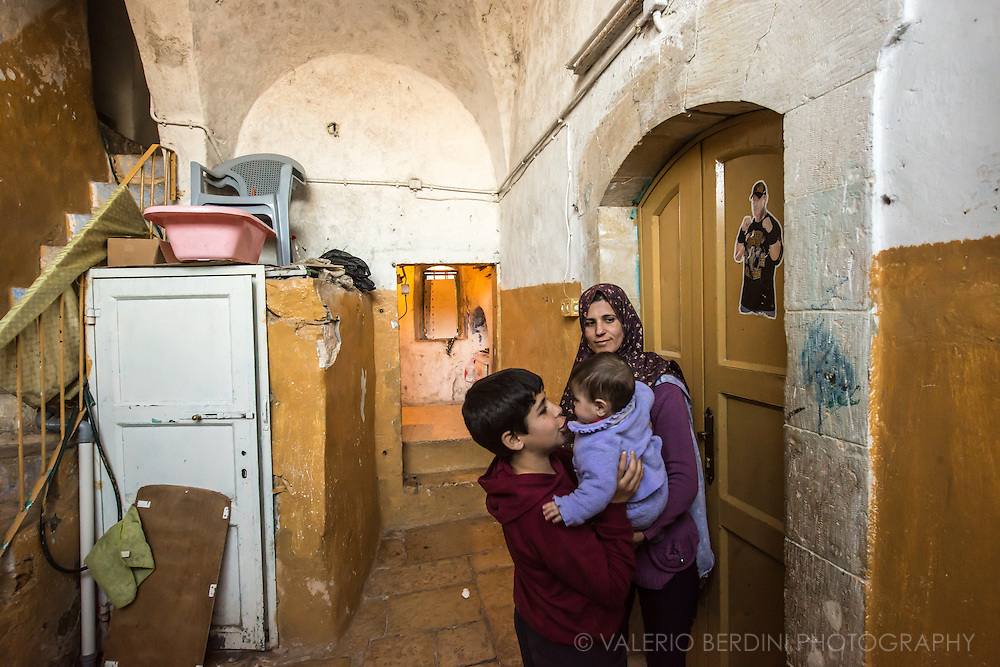 A Palestinian family in a house bordering a Jewish settlement in Hebron. The window in the room on the back is obscured by a board to avoid contact with the Israeli occupiers.