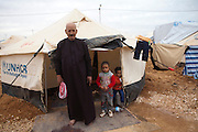 Syrian refugee Abu Moa'ad with two of his children by their tent at the  Al-Zaatri refugee camp in the Jordanian city of Mafraq, near the border with Syria ,February 5,2013. He fled with his family from Daraa, Syria after his son and daughter were killed by snipers .He was smuggled into Jordan by car and then by walking to the border ...Jordan announced on Tuesday that the number of Syrian refugees in the country is expected to exceed 700, 000 in 2013, the state-run Petra news agency reported. (Photo by Heidi Levine/Sipa Press).