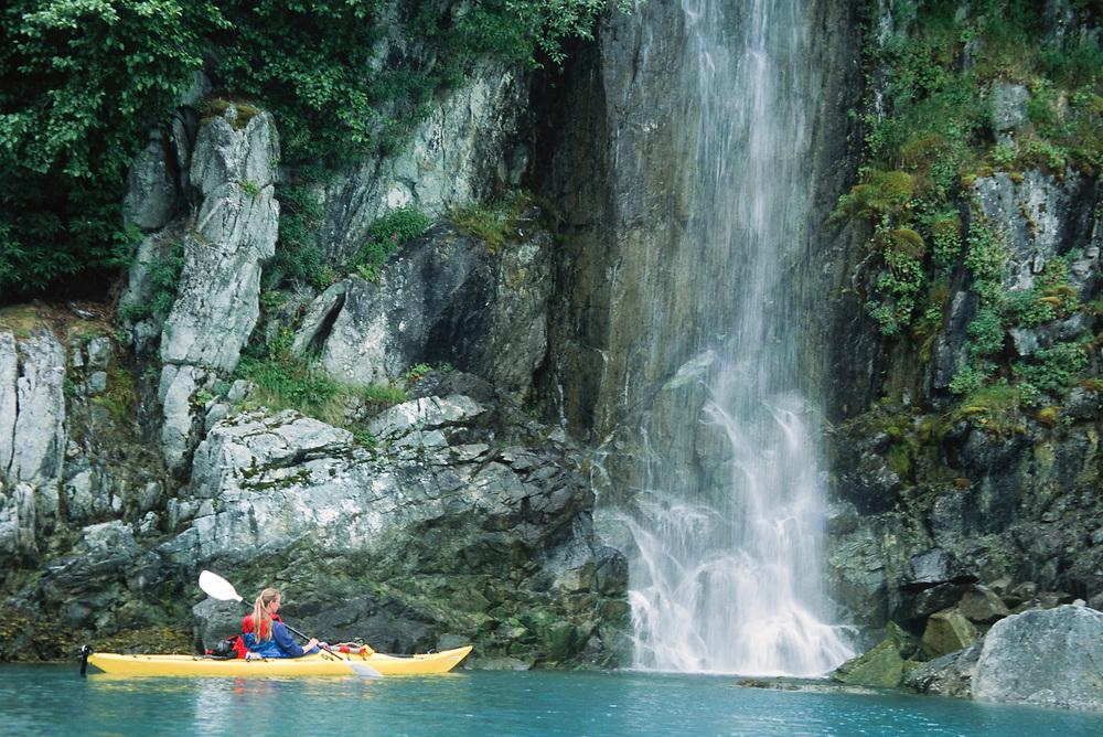 Alaska. Glacier Bay NP. A kayak paddles up to a an unnamed waterfall in Gilbert peninsula.