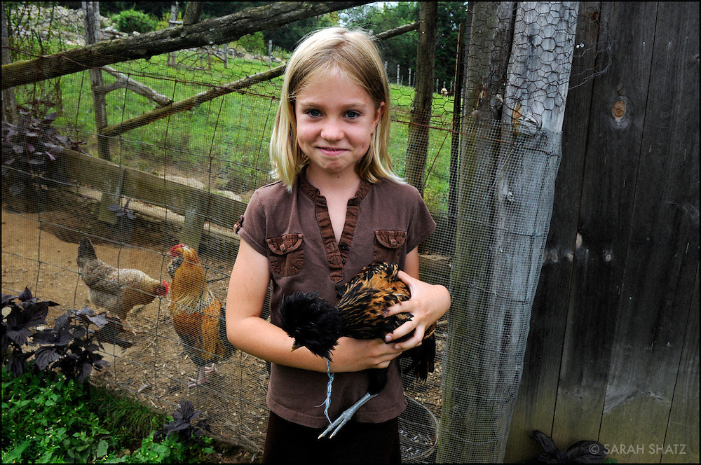 Girl with bird at chicken coop