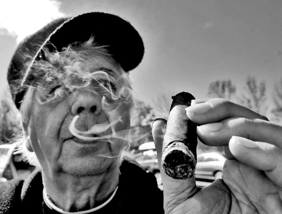 (photo by Matt Roth)..Al Paglione takes reprise from cooking during the 2006 Eddie Adams Workshop to chomp on a Cuban cigar...This is Al Paglione. He and his son help cook at the Eddie Adams Workshop. Meeting him was pretty great! I was shooting him with my 17-55mm and he was totally jockin' me about my zoom. He was talking up the Nikon 50 f/1.4 -- which I have -- and so, I decided to take that lens out of my bag and snap it on my camera for a spin. So, everything after this photo are shot with the 50mm. He was right, that lens is awesome...I gave a print of this photo to Al's son Jerry, and he started crying and gave me a huge hug. Those two bicker like the Jersey boys they are, but there's so much love between the two of them...The Eddie Adams Workshop in Jeffersonville Saturday, October 7, 2006.