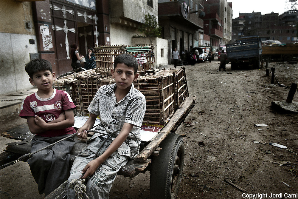 "Young's  ""Zabbaleen"" collector in a Mokattam street with his carriage.On the outskirts of Cairo in the middle of Manshiet Nasr neighborhood is located Mokattam settlement known as ""Garbage City"" is inhabited by Zabbaleen, a community of about 45,000 Coptic Christians living for decades to recycle waste generated by the Egyptian capital: plastic, aluminum, paper and organic waste transformed into compost. Most part of the Association for the Protection of the Environment (APE), an NGO that works in the area, whose objectives are to protect the environment and improve the livelihoods of garbage scavengers in Cairo. According to the UN, the work is done in Mokattam is one of the ten best examples of world environmental improvement. El Cairo , Egipt, June 2011. ( Photo by  Jordi Camí )."