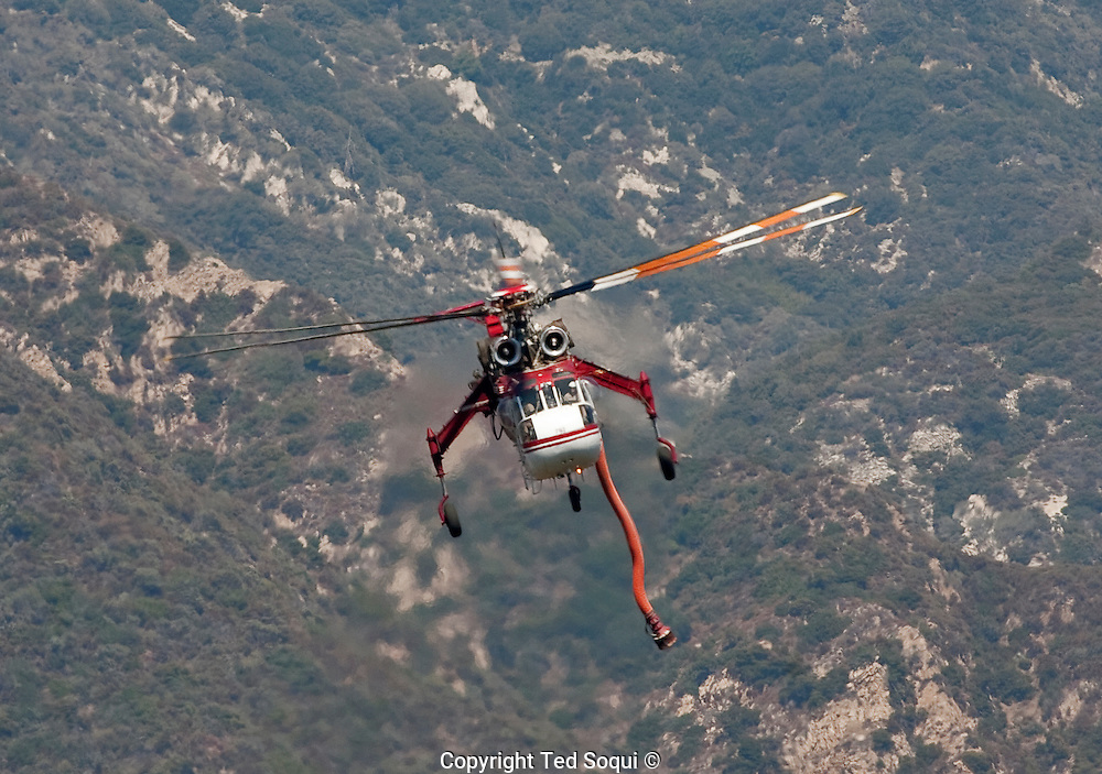 A Skycrane firefighting helicopter flies above the hills of La Canada..The Station fire burns in the hills above Los Angeles. The city has experienced above normal summer temperatures and low humidity. This is a fuel driven fire, no Santa Ana winds are expected till late September