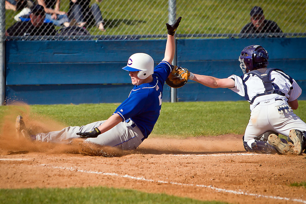 Coeur d'Alene High's Kaleb DeHaas unsuccessfully tries to avoid the tag from Bryce Mort from Lake City High as he slides toward home plate.