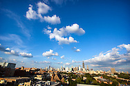 A few puffy summer afternoon clouds roll over the famous Chicago skyline, as seen from the west side of the city on a warm day.