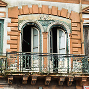 """An old building with balcony. In La Boca barrio (neighborhood) of Buenos Aires, tourists are attracted by colorful houses, the Caminito pedestrian street, La Ribera theatre, tango clubs, and Italian taverns. La Boca retains a strong European flavor, with many early settlers from Genoa, Italy. It sits at the mouth (""""boca"""" in Spanish) of the Matanza River (or Río Mataderos, or Riachuelo which simply means ?Creek?). La Boca is known among sports fans for La Bombonera stadium (Estadio Alberto J. Armando), home of Boca Juniors, one of the world's best known football (soccer) clubs. As a centre for radical politics, La Boca elected the first socialist member of the Argentine Congress (Alfredo Palacios in 1935) and hosted many demonstrations during the crisis of 2001 in Argentina, South America."""