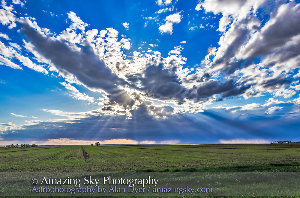 Crepuscular rays of sunlight streaming from behind approaching storm clouds over the Alberta prairie and a planted spring field, May 2014. This is a high-dynamic range stack of 5 images.