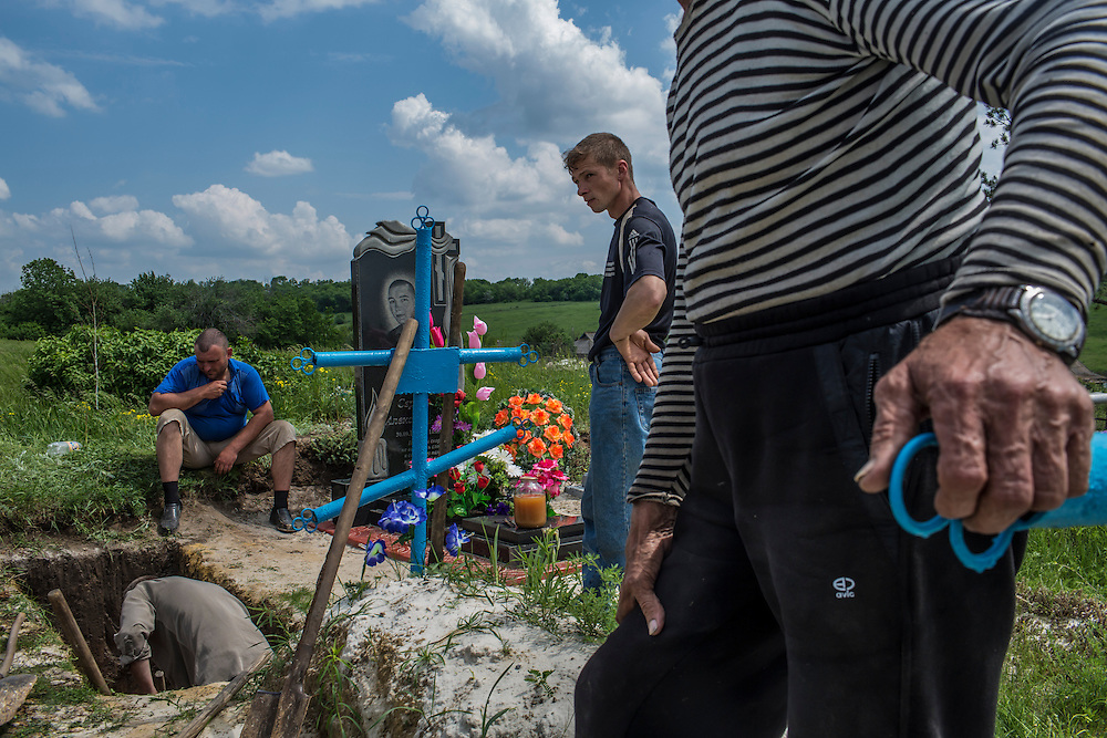 STAROVARVAROVKA, UKRAINE - MAY 15:  Friends and relatives of Lena Ott, 42, dig her grave in a cemetery on May 15, 2014 in Starovarvarovka, Ukraine. Ott was killed the prevoius night when the car she was riding in was fired on by forces her family believes to be the Ukrainian military. (Photo by Brendan Hoffman/Getty Images) *** Local Caption ***