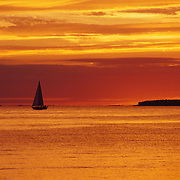 Sailboat at Sunset near Egg Harbor, Wisconsin in Door County.  Door County on the Door Peninsula in Wisconsin is a popular vacation location in the Midwest.  The Peninsula is south of the Upper Peninsula of Michigan.  It offers a great place to relax and enjoy nature. Door County has five state parks, ten lighthouses, and beautiful sandy beaches with the fresh, clear water of Lake Michigan.