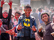 """12 MARCH 2017 - BHAKTAPUR, NEPAL: People celebrate Holi in """"Pottery Square"""" in Bhaktapur by throwing colorful powder on each other and dousing each other with water. Holi, a Hindu religious festival, has become popular with non-Hindus in many parts of South Asia, as well as people of other communities outside Asia. The festival signifies the victory of good over evil, the arrival of spring, end of winter, and for many a festive day to meet others. Holi celebrations in Nepal are not as wild as they are in India.     PHOTO BY JACK KURTZ"""