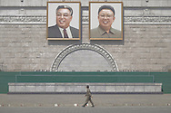 """A man walks under giant portraits of the """"Eternal Leader"""" and the """"Dear Leader"""", on Pyongyang's Kim-Il Sung Square, a place of great cultural significance, as it is a common gathering place for rallies, dances and military parades. Both Kims are now dead and the DPRKs current ruler is the third in the dynasty, Kim Jong-un, the son of Kim Jong-il and the grandson of Kim Il-Sung. In April 2012, Kim Jong-un was formally given the title of Supreme Leader. He is not even 30 years old."""