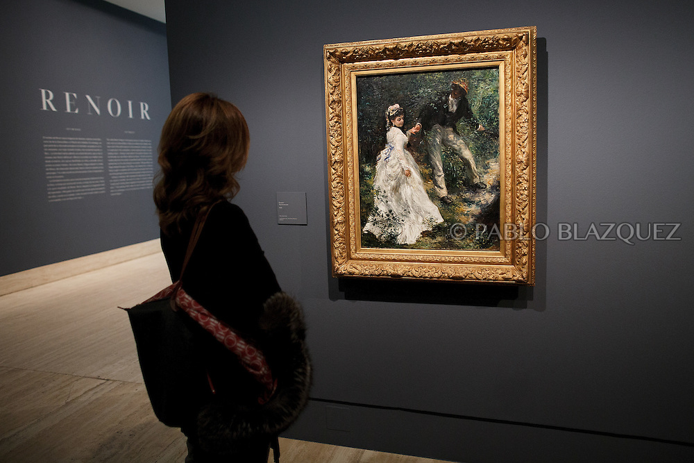 A member of the press looks at Pierre Auguste-Renoir's work 'The Promenade', painted in 1870 and borrowed from the J. Paul Getty Museum, at the Museum Thyssen-Bornemisza on October 17, 2016 in Madrid, Spain. 'Renoir: Intimacy' features 78 works by French painter Renoir (1841-1919) borrowed from museums and collections from around the world and will be open to the public from October 18, 2016 to January 22, 2017 (© Pablo Blazquez)