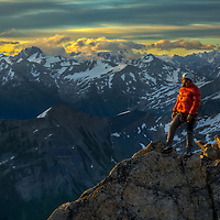 Alex Pedneault watches sunrise on the summit of East Post Spire, Bugaboo Provincial Park, British Columbia, Canada