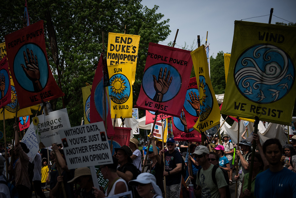 People carry signs as they take part in the Climate March in Washington, D.C. on April 29, 2017. CREDIT: Mark Kauzlarich for CNN