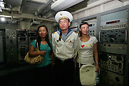 """A North Korean sailor poses for a snapshot with Chinese tourist aboard the American ship """"Pueblo"""" captured by North Korea, now docked in Pyongyang, North Korea Sunday Aug. 5, 2007. The leaders of North and South Korea will meet this month for the second time since the peninsula's division after World War II, capitalizing on progress in Pyongyang's nuclear disarmament to revive their historic reconciliation.(AP Photo/Elizabeth Dalziel)"""