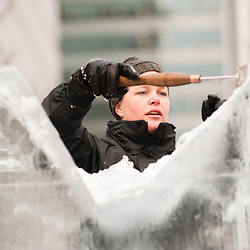 London, UK - 11 January 2012: a sculpture works a block of ice with his chisel during the Ice sculpting festival 2013 in Canary Warf.