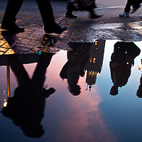 Passerby's reflect in rain water in front of the Koutoubia minaret, the main landmark of Marrakesh.