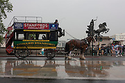 A horse-drawn omnibus advertising travel bookshop Stanfords stands at traffic lights in Westminster alongside the famous statue of Iceni rebel queen Boudicca (Boadicea).