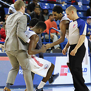 Delaware 87ers Head Coach Kevin Young helping Forward Malcolm Lee (14) who was suffering from severe leg cramps in the first half of a NBA D-league regular season basketball game between the Delaware 87ers and the Westchester Knicks (New York Knicks) Sunday, Dec. 28, 2014 at The Bob Carpenter Sports Convocation Center in Newark, DEL