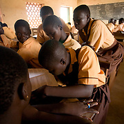 A group of students gather around a single schoolbook during a class at the Savelugu Junior Secondary School in Savelugu, Ghana on Tuesday June 5, 2007.