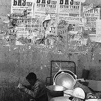 A stall holder in Chorsu Bazaar, selling metal pots and pans, reads the newspaper,  Bishkek,  Kyrgyzstan.