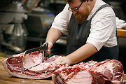 SHOT 8/14/13 6:59:53 PM - Justin Brunson, Owner and Executive Chef at Old Major, butchers half a hog into specific cuts at the restaurant in Denver, Co. The pigs are raised locally in Brush, Co. and Brunson buys two a week that he then butchers in-house and uses the entire hog in various dishes in the restaurant. The restaurant focuses on heritage-raised meats from Colorado farms, features an in-house butchery program and bills itself as contemporary farmhouse cuisine. (Photo by Marc Piscotty / © 2013)