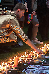Church of St. Ann, Soho, London, June 13th 2016. Thousands of LGBT people and their friends converge on Old Compton Street in London's Soho to remember the fifty lives lost in the attack on gay bar Pulse in Orlando, Florida. PICTURED: A mourner places a candle in the yard of Church of St. Ann, Soho.