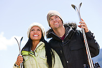 A man and a woman holding their downhill skis.