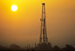 Stock photo of on-shore rig at sunset