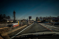 Police officer watches northbound traffic on National Route 6 where the highway enters the nuclear no-entry zone, to be sure cars stay on the highway (drivers are forbidden to take any side roads or stop within the no-entry zone).  Tomioka, Fukushima Prefecture, Japan.