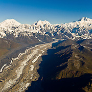 Over Tokositna Glacier, fly towards Mounts Foraker, Hunter, and McKinley/Denali in Denali National Park and Preserve, Alaska, USA. See a vast wilderness of glaciers, icy peaks, and mile deep granite gorges in the Alaska Range. Denali (20,310 feet or 6191 meters, aka Mount McKinley) is the highest mountain peak in North America. Measured from base to peak, it is earth's tallest mountain on land. Mount McKinley is a granitic pluton uplifted by tectonic pressure while erosion has simultaneously stripped away the softer sedimentary rock above and around it.