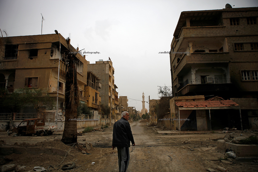 A man walks through his destroyed neighbourhood in Deir az-Zor. Residents of eastern syrian town Deir az-Zor joined arab spring protests against the regime of Bashar al-Assad from its early beginning in March 2011. Since summer 2012 the town with few hundred thousand inhabitants is embattled between the Syrian Army and different opposing rebel groups like Free Syrian Army and Jabhat al-Nusra. Deir az-Zor is target to constant shelling by artillery, war planes and short range missiles. Almost 70 percent of the town is rebel held while government forces remain in control over some residental areas and a strategic important airport. Deir az-Zor is widely damaged and some areas almost totally destroyed by fierce and long lasting battles. All direct road connections to Deir az-Zor are cut and fighters and returning residents as well depend on one provisional supply line across the Euphrates river which is regularly targeted by government snipers.