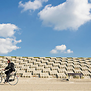 A cyclist cycling along the 5.5 km (3.5 miles) long artificial sea defence or dike. This dike is known as the Hondsbossche zeewering (sea protection) and stretches between the towns of Schoorl and Petten as a protection during high tides of the North Sea.