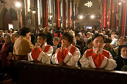 """Chinese Christians pray during a mass for Easter April 7, 2007 in Beijing, China.  Chinese are largely flocking to traditional religions such as Buddhism and Taoism, many are also turning to Christianity and there are now around 10 million or more Catholics in China -- with about a third belonging to an """"underground"""" church that has remained loyal to the Vatican despite decades of harsh repression under the Communist Party. (Photo by Ami Vitale)"""