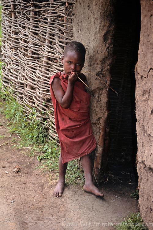 Africa, Kenya, Maasai Mara. A young child stands at the door of his boma, a traditional Maasai home.