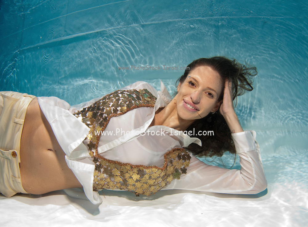 A young trendy dressed woman floats underwater Model release available