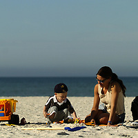 (02.03.2005)(PHOTO/CHIP LITHERLAND) --Lenka Eckert of Germany, and her son, Rico, 2, play with tractors in the sand while on their 5-week vacation at Manatee Public Beach in Holmes Beach on Anna Maria Island Thursday, February 3, 2005.