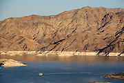 A houseboat on Callville Bay cruises by a shoreline bathtub ring in Lake Mead National Recreation Area, Nevada, USA. Formation of Lake Mead began in 1935, less than a year before Hoover Dam was completed along the Colorado River. The area surrounding Lake Mead was established as the Boulder Dam Recreation Area in 1936. In 1964, the area was expanded and became the first National Recreation Area established by US Congress. Three desert ecosystems meet in Lake Mead NRA: Mojave Desert, Great Basin Desert, and Sonoran Desert.