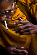 A funky monk smokes a cigarette at an outdoor market in Bangkok, Thailand. No religious edict bans Buddhists from smoking, but a government report identified cigarettes as the leading cause of death among monks in Thailand.