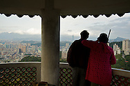 A couple looks across Taipei from Lion's Head mountain in Xindian City, Taiwan.