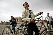 Afghan youths ride their bikes on the edge of Kabul, Afghanistan.