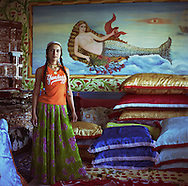 Cassinca, 18 years old married Roma girl, stands in front of a mermaid painted on the wall of a new home, in the new part of the camp. Mermaids are very popular as wall decoration, but no-one within the camp knows the reason why they were first painted.