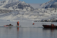 Scientists work atop frozen fjord collecting data about local ice and carbon cycle; Kongsfjorden, Svalbard, Norway.