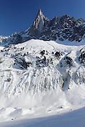 Skiers below Aiguille du Dru, on the Mer de Glace Glacier, near Chamonix, French Alps.