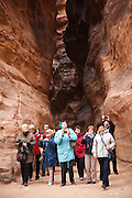 A group of tourists look up and photograph The Treasury (Al Khazneh) in Petra, Jordan.