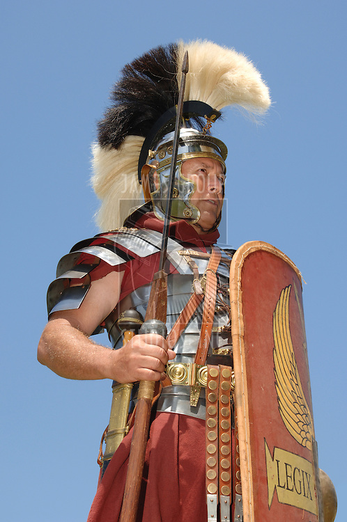 1st century Roman soldier in armour, rank of Optio shot against a blue sky