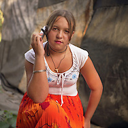 A young Roma girl sits, posing with her mobile telephone, beside a tent in the old part of Sintesti Roma camp..